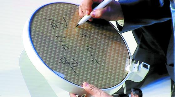 문재인 대통령이 2019년 4월 30일 삼성전자 화성공장에서 열린 '시스템 반도체 비전선포식'에서 웨이퍼에 서명하고 있다. 이 웨이퍼는 세계 최초로 극자외선 공정을 거쳐 출하됐다. [중앙포토]