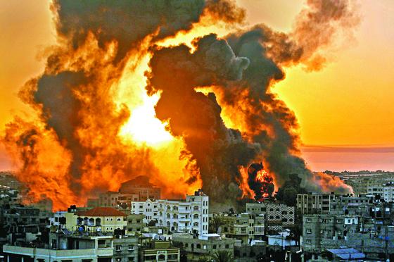 지난 12일 이스라엘군 공습으로 팔레스타인 자치지구인 가자시 남부의 칸 유니쉬 지역에서 검은 연기와 함께 불길이 타오르고 있다.
