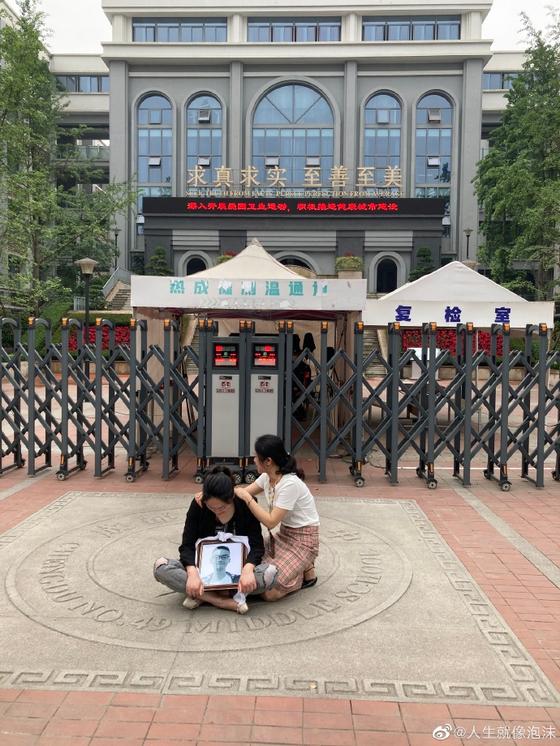 지난 10일 오전 중국 청두의 제49중 교문 앞에서 전날 의문의 추락사로 숨진 린 모군의 어머니 루 씨가 아들의 영정을 품에 안고 오열하고 있다. [루씨 웨이보 캡처]