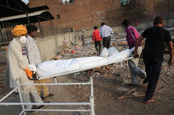 인도 뉴델리의 한 화장장에서, 코로나19 감염으로 사망한 환자의 시신을 운구하고 있는 가족과 화장장 관계자. [EPA=연합뉴스]