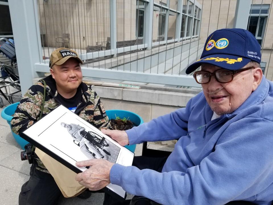 라미 현 작가가 촬영한 사진 액자를 휠체어에 앉은 한 미군 참전용사에게 건네고 있다. 미국 워싱턴D.C.의 '참전용사마을'(AFRH·Armed Forces Retirement Home)에서. [사진제공=라미 현]