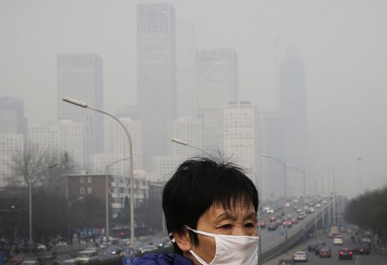 2015년 12월 스모그가 짙게 낀 거리를 마스크를 착용하고 걷는 중국 베이징 시민. AP=연합뉴스