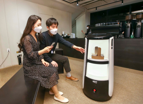 서울 종로구 광화문 D타워에서 우아한형제들의 실내 자율 주행 배달 로봇의 커피 배달 모습. [사진 우아한형제들]