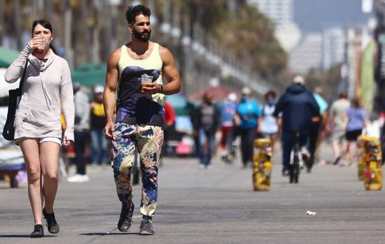 지난달 28일(현지시간) 미 캘리포니아의 베니스 비치에서 마스크를 쓰지 않은 사람들이 지나가고 있다. AFP=연합뉴스