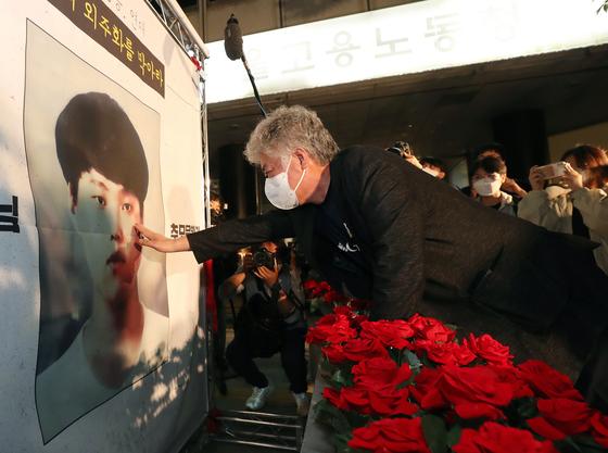 고 이선호군 아버지 이재훈씨가 지난 13일 중구 서울지방고용노동청 앞에서 열린 고 이선호군 추모문화제에서 이군 사진 앞에 놓인 컨테이너모형에 장미꽃을 놓은 후 사진을 어루만지고 있다. 뉴스1