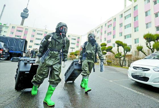 육군 제2작전사령부 소속 19화생방대대 장병들이 지난해 3월 코호트 격리 주거시설인 대구 달서구 한 아파트에서 방역작전을 펼치고 있다. 당시 신천지 신도가 거주하는 이 아파트에서 신종 코로나바이러스 감염증(코로나19) 확진자가 여러명 나왔다. 뉴시스
