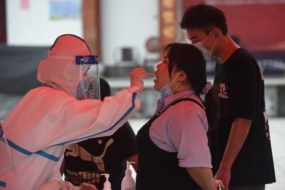 15일 중국 안후이성 루안시의 한 시민이 방역 요원에게 코로나19 핵산검사를 받고 있다. 중국은 13일 안후이성에서 2명의 신규 확진자가 발생한 이후 사흘간 26명의 감염자가 발생하는 등 지역 감염 우려가 높아지고 있다. [신화=연합뉴스]