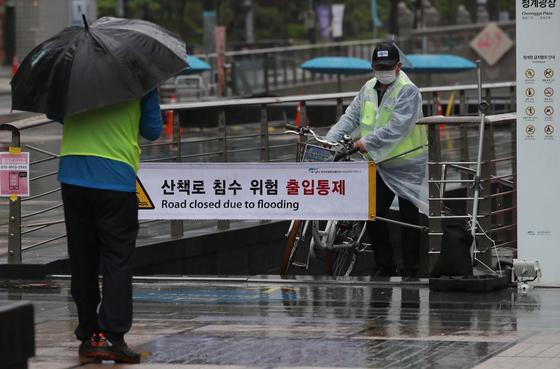 16일 오전 서울 청계천 산책로가 침수 위험으로 출입이 통제, 서울시설공단 관계 근무자들이 순찰을 돌고 있다. 16일 전국에 비가 이어지고, 남부지방을 중심으로는 강하고 많은 비가 내릴 것으로 보인다. 뉴스1