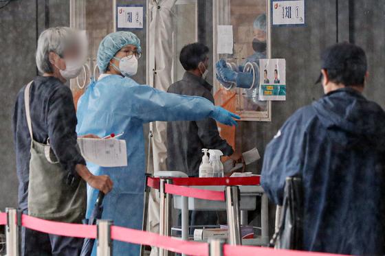 16일 오전 서울 중구 서울역광장에 마련된 코로나19 임시선별검사소를 찾은 시민들이 진단검사를 받고 있다. 뉴스1