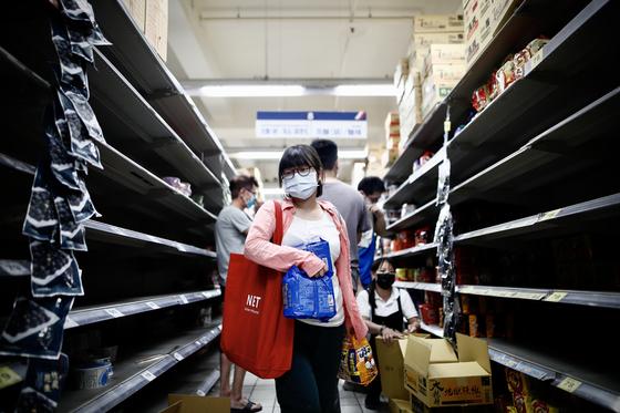 하루 신규확진자가 처음으로 세 자리수가 나온 대만에서 지난 15일 한 식료품점에서 생필품을 구매하는 이들이 몰리면서 매대가 비어있는 모습 [EPA=연합뉴스]