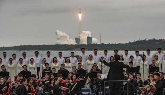 지난달 29일 중국 하이난성 원창 기지에서 우주정거장 핵심 모듈 '톈허'(天和)를 실은 창정 5B 로켓이 성공적으로 발사되는 가운데 시안 심포니 오케스트라와 합창단의 공연이 펼쳐지고 있다. 모듈 톈허는 우주정거장의 궤도를 유지하기 위해 추진력을 내는 기능과 함께 향후 우주 비행사들이 거주할 생활 공간을 갖추고 있다. 중국은 올해와 내년에 모두 11차례 걸친 발사로 모듈과 부품을 실어날라 독자적으로 우주정거장을 건설한다는 계획이다. [EPA=연합뉴스]