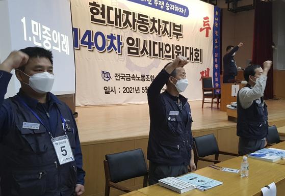 현대자동차 노조원들이 지난 12일 울산 북구 현대차 문화회관에서 열린 임시 대의원대회에서 구호를 외치고 있다. [뉴스1]