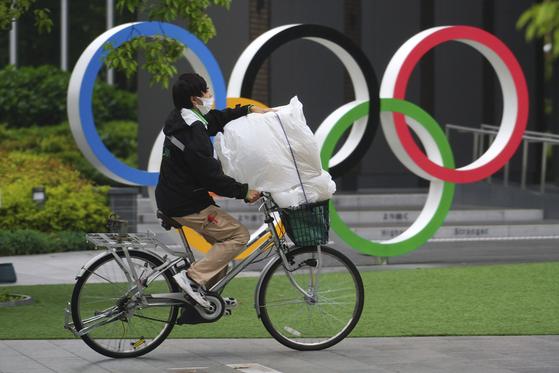 13일 마스크를 쓴 시민이 일본 도쿄의 오륜마크 앞을 지나고 있다. [AP=연합뉴스]