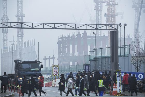 삼성전자와 협력업체 직원들이 경기도 평택에 있는 삼성전자 평택캠퍼스로 출근하고 있다. 도로 뒤쪽으로 건설 중인 반도체공장이 보인다. 전민규 기자