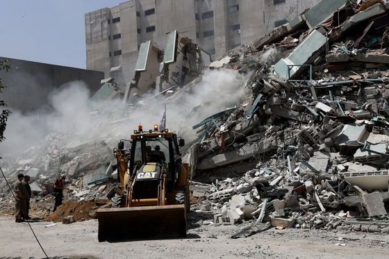 16일(현지시간) 현장 인부들이 AP통신 등 언론사들이 입주했던 건물의 파괴된 잔해를 치우고 있다. AP통신=연합뉴스