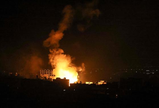 16일(현지시간) 새벽 팔레스타인 자치 지역인 가자지구 남부 라파 마을 상공에서 이스라엘군이 발사한 폭탄이 터지고 있다. [AFP=연합뉴스]