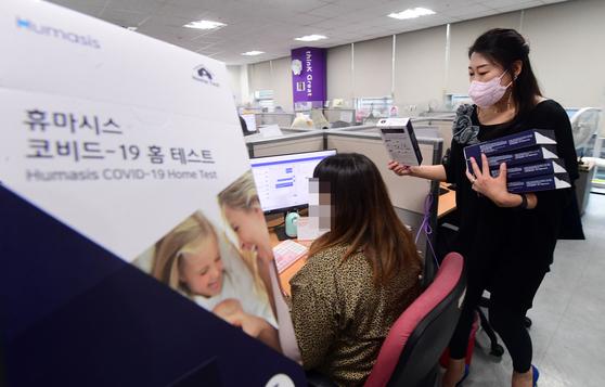 17일 오후 서울 성동구의 한 콜센터에서 센터 관계자가 직원들에게 신종 코로나바이러스 감염증(코로나19) 신속 자가진단 키트를 배포하고 있다. [연합뉴스]