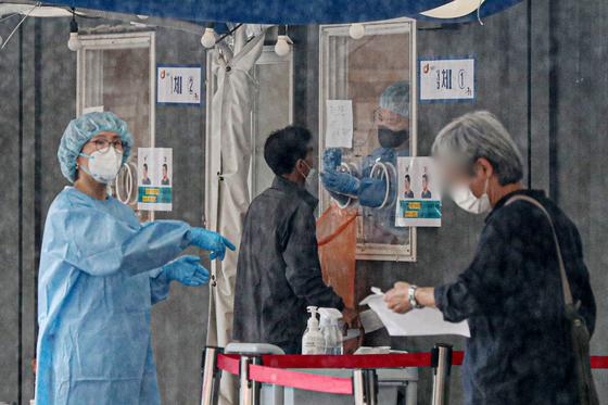 지난 16일 오전 서울 중구 서울역광장에 마련된 코로나19 임시선별검사소를 찾은 시민들이 진단검사를 받고 있다. 뉴스1
