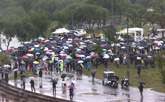'16일 오후 서울 반포한강공원 수상택시 승강장 인근에서 열린 '고 손정민 군을 위한 평화집회'에서 참가자들이 우산을 쓴 채 자리를 지키고 있다 연합뉴스
