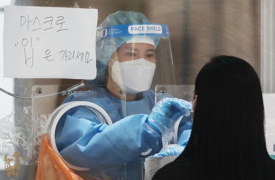 지난 17일 서울 중구 서울역 광장에 마련된 신종 코로나바이러스 감염증(코로나19) 임시선별검사소에서 의료진이 검체 검사를 하고 있다. 뉴스1