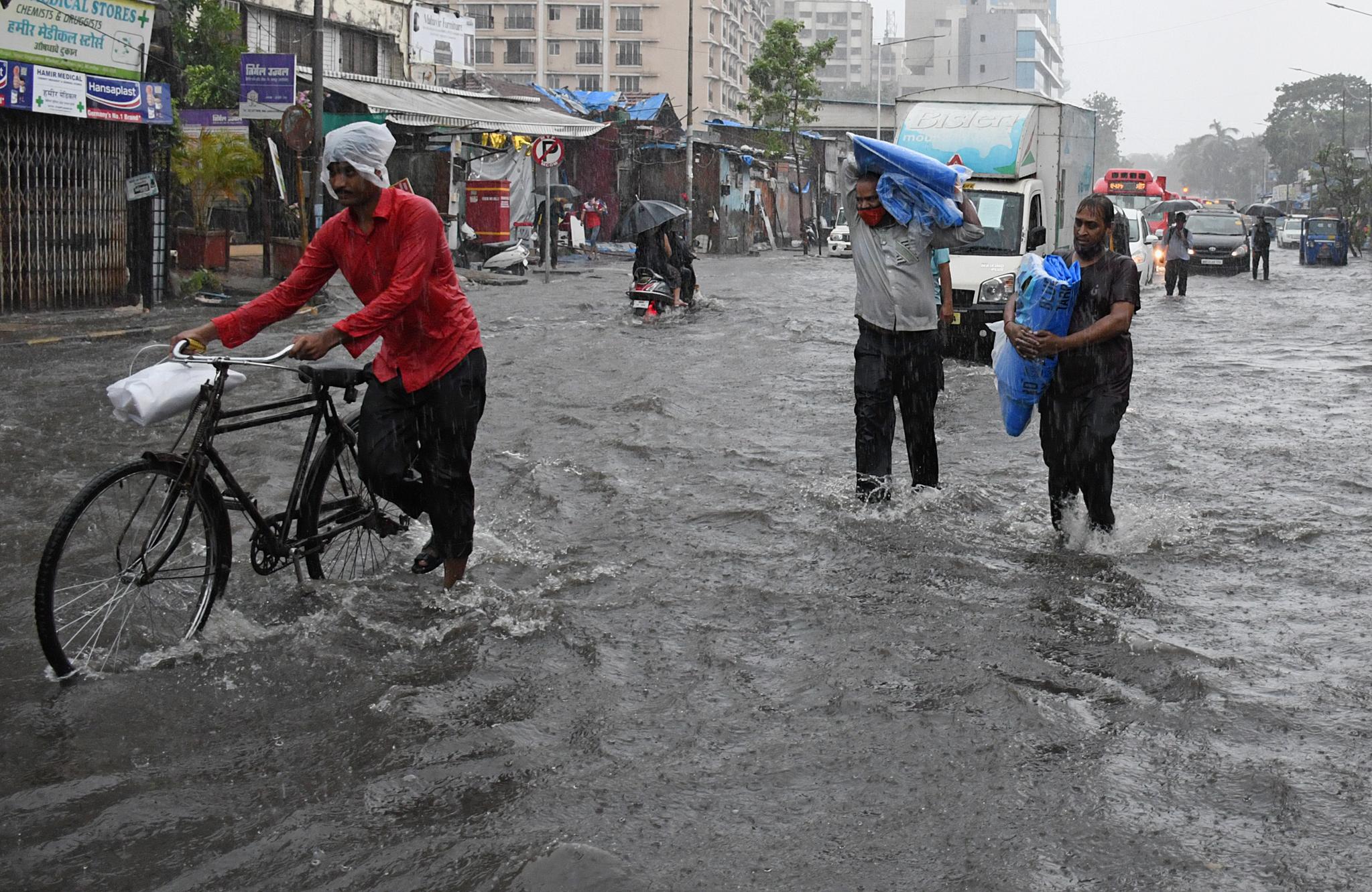 17일(현지시간) 사이클론 타우크테가 몰고온 폭우로 뭄바이 등 인도 서부 지역에 폭우가 내렸다. 도로가 침수된 가운데 시민들이 대피하고 있다. EPA=연합뉴스