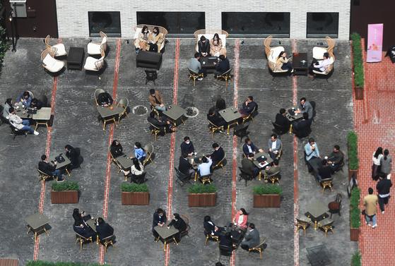 서울 중구 청계천 인근 커피숍 야외 테라스에서 점심을 마친 직장인들이 커피를 마시고 있다. 연합뉴스