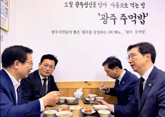 더불어민주당 송영길 대표(왼쪽 두 번째)와 국민의힘 김기현 대표 권한대행 겸 원내대표(오른쪽 두 번째)가 18일 5·18민주화운동 제41주년 기념식에 참석하기에 앞서 광주 한 식당에서 주먹밥을 먹으며 대화하고 있다. 송영길 대표 페이스북