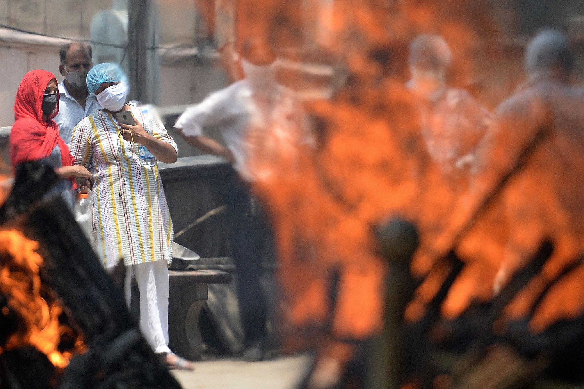 15일(현지시간) 인도 뉴델리의 한 화장장에서 유족들이 신종 코로나바이러스 감염증(코로나19)으로 사망한 환자의 장례식을 치르고 있다. AFP=연합뉴스