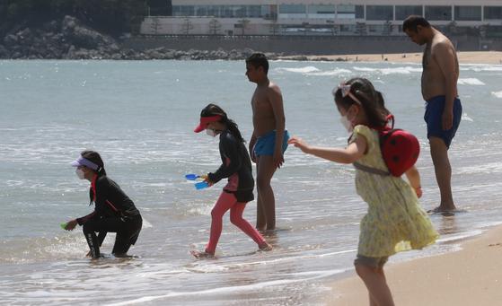 전국적으로 초여름 날씨를 보인 13일 부산 해운대해수욕장에서 외국인 관광객과 어린이가 물놀이를 하며 더위를 식히고 있다. 송봉근 기자