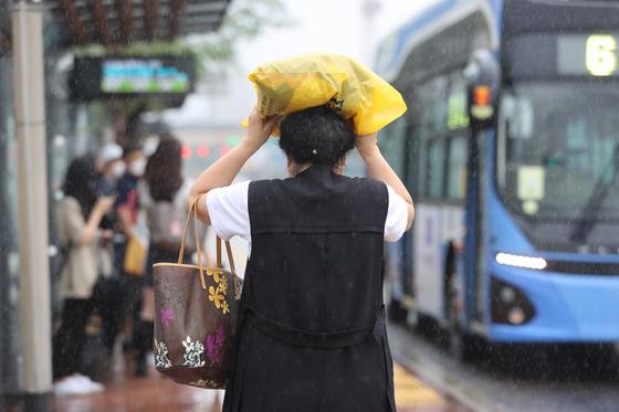 많은 비가 내린 16일 오전 서울 서초구 고속터미널역 인근에서 한 시민이 비닐봉지로 비를 피하며 뛰고 있다. 연합뉴스