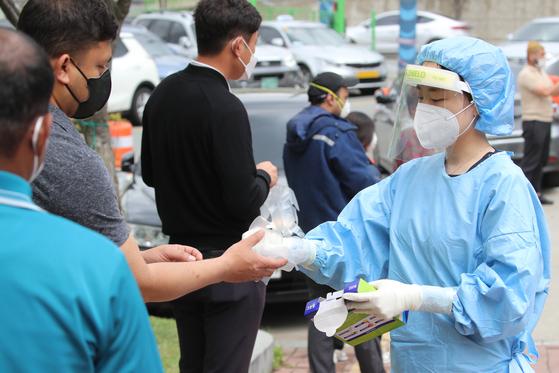 18일 오후 대구 서구보건소 관계자가 선별진료소에서 코로나19 검사를 기다리는 외국인에게 비닐 장갑을 나눠주고 있다. 뉴스1