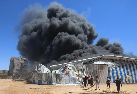 18일(현지시간) 가자지구의 한 창고가 이스라엘의 공습으로 불타오르고 있다. 신화=연합뉴스