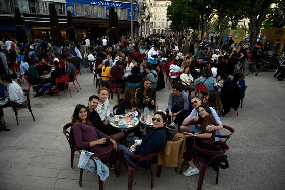 신종 코로나바이러스 감염증(코로나19)으로 폐업한 프랑스 전역에 카페, 레스토랑 등 업소가 다시 문을 열면서 19일(현지시간) 프랑스 남부 마르세유에 있는 한 카페 테라스에 사람들이 모여 음료를 마시고 있다. AFP=연합뉴스