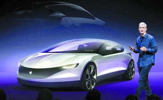 팀 쿡 애플 CEO가 주주들과의 연례 모임에서 미래 자동차 산업과 애플의 '아이카(iCAR)' 콘셉트 이미지를 소개하고 있다. [로이터]