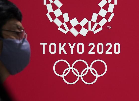 마스크를 쓴 도쿄시민과 올림픽 엠블럼. [EPA=연합뉴스]