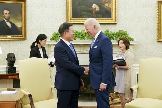 문재인 대통령과 조 바이든 미국 대통령이 21일 오후(현지시간) 워싱턴 백악관 오벌오피스에서 열린 소인수회담에서 웃으며 악수하고 있다. 뉴스1