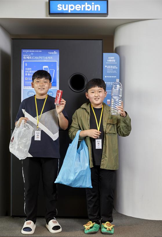 소셜 벤처 '수퍼빈' 본사를 찾은 김승윤(왼쪽)·김지성 학생기자가 집에서 가져온 캔·페트병을 들고 AI 순환자원 회수로봇 '네프론' 앞에 섰다.