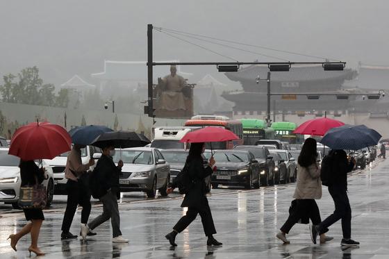 전국 대부분 지역에 '황사비'가 내린 25일 오전 서울 종로구 광화문 네거리에서 우산을 쓴 시민들이 출근길 발걸음을 재촉하고 있다. 뉴스1