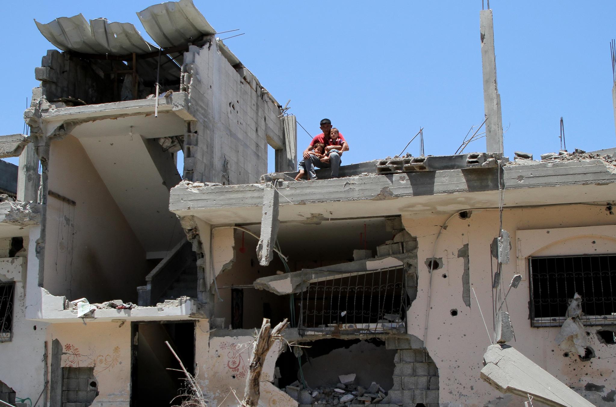 24일(현지시간) 가자지구 북동부 베이트 하눈의 뼈대만 남은 집 옥상에서 한 남성이 두 아들을 안고 있다. 삶의 터전이 열흘간의 전쟁으로 돌무더기로 변했다. 신화=연합뉴스
