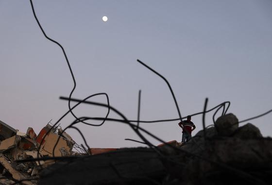 5월 24일 가자지구의 가자시티에서 한 남자가 이스라엘의 폭격으로 무너진 건물 잔해를 배경으로 서서 달을 바라보고 있다. AFP=연합뉴스