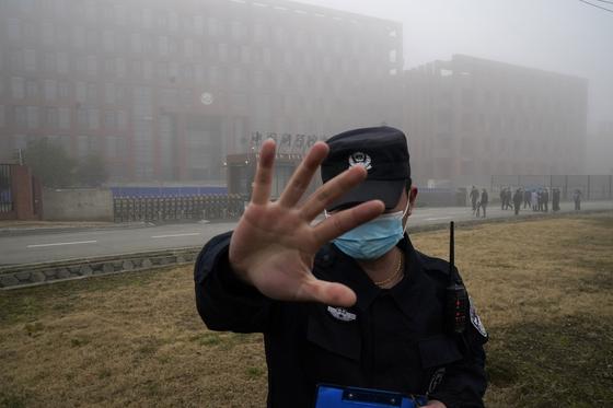 지난 2월 중국 후베이성의 우한 바이러스 연구소(WIV) 앞 에서 보안 요원이 세계보건기구(WHO) 코로나19 기원 조사팀을 취재하려는 외신 기자들의 접근을 막고 있다. [AP=연합뉴스]