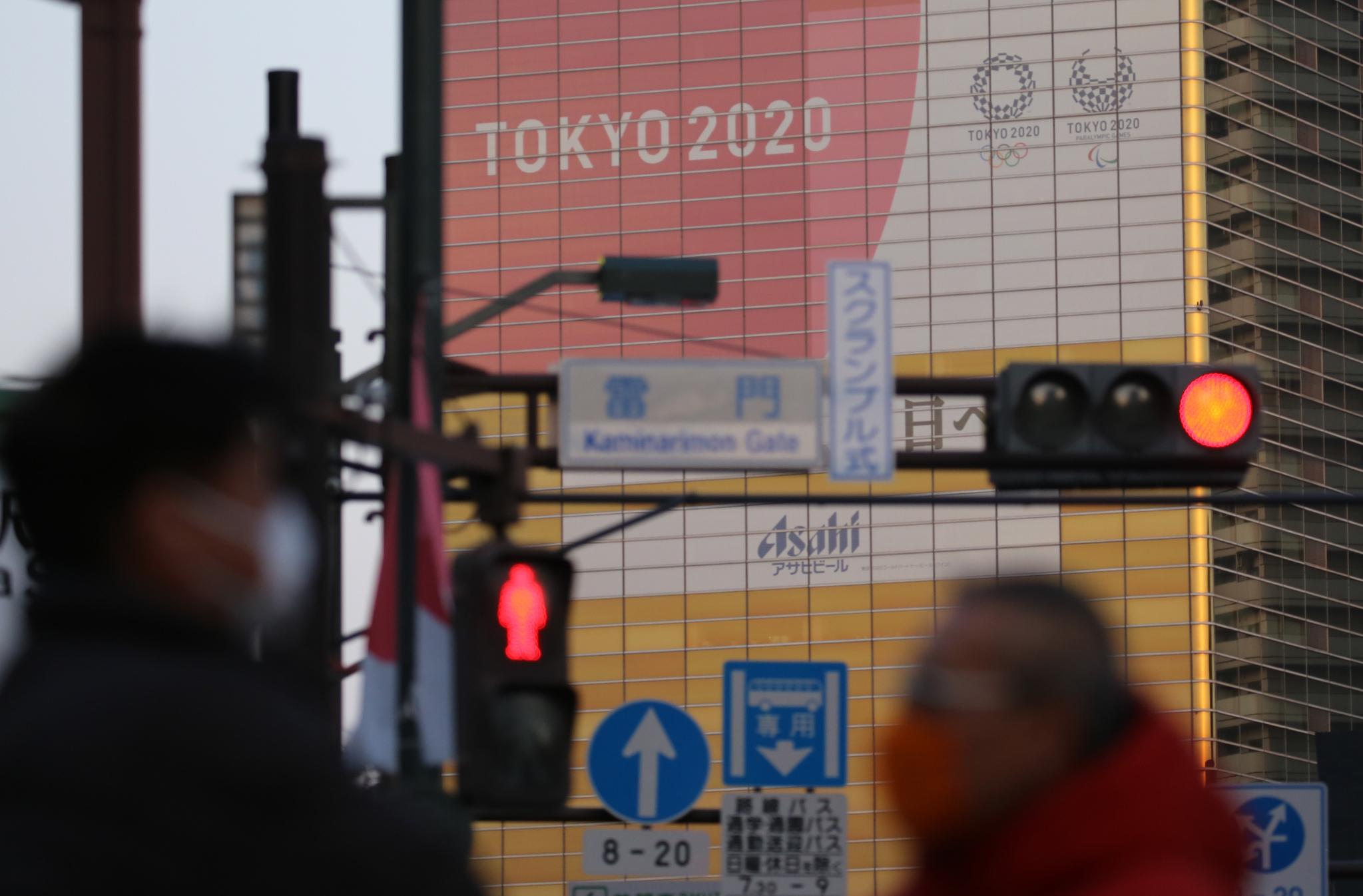 일본 도쿄도 스미다(墨田)구의 한 건물에 도쿄올림픽 홍보물이 설치된 가운데 근처에 보이는 신호등에 적신호가 켜져 있다. 연합뉴스