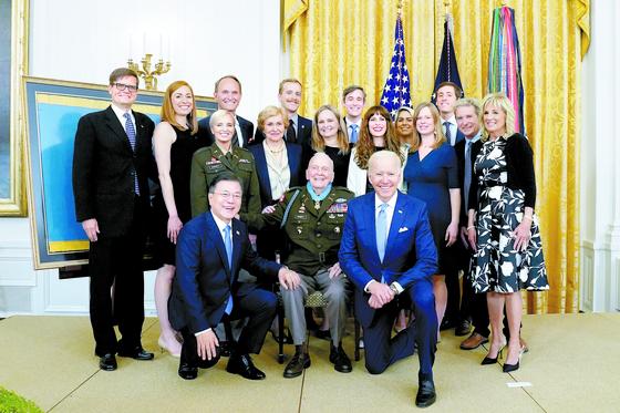 문재인 대통령이 21일 오후(현지시간) 백악관 이스트룸에서 열린 한국전쟁 명예 훈장 수여식에서 조 바이든 미국 대통령, 랠프 퍼켓 주니어 예비역 대령 가족과 기념촬영을 하고 있다. 연합뉴스