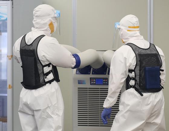 서울 송파구 보건소 선별진료소에서 의료진이 냉풍기 바람을 쐬며 더위를 식히고 있다. 연합뉴스