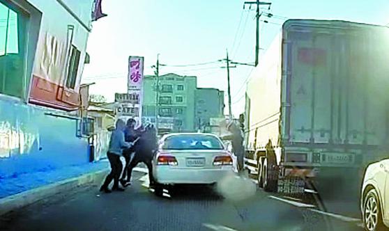 지난 8일 경기 화성시의 한 도로에서 주행 중인 차량 앞을 가로막은 일당이 둔기로 차량을 부순 뒤 운전자와 동승자를 폭행하는 사건이 발생해 경찰이 수사에 나섰다.   사진은 폭행 장면이 담긴 블랙박스 영상. 연합뉴스
