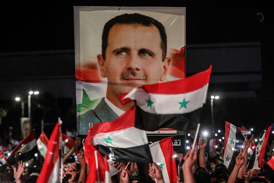 시리아 대선에서 바샤르 알아사드 시리아 대통령이 95.1%의 득표율로 4선에 성공했다. 5월 27일 시리아에서 지지자들이 그의 사진과 국기를 들고 축하하는 모습 [AFP=연합뉴스]