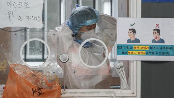 지난 27일 오전 서울 중구 서울역에 설치된 임시 선별검사소에서 검사 담당 관계자가 방호복을 고쳐 입고 있다.   연합뉴스