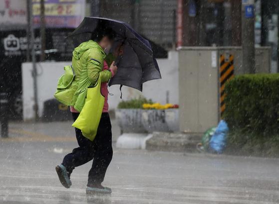 28일 오후 울산 남구 한 거리에서 시민이 우산을 부여잡고 걷고 있다. 뉴스1