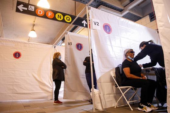 12일(현지시간) 미국 뉴욕 브루클린의 코니아일랜드 지하철역에 문을 연 임시 백신접종소에서 한 시민이 코로나19 백신을 접종받고 있다. 뉴욕시는 16일까지 6개 전철역의 임시 접종소에서 관광객 등을 대상으로 무료 접종 서비스를 실시한다. [로이터 연합뉴스]