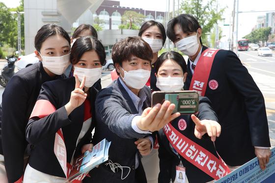 국민의힘 당 대표 출마를 선언한 이준석 전 최고위원이 24일 오후 대구 북구 경북대학교 북문 앞에서 대학생들과 인사 나누며 기념사진을 찍고 있다. 뉴스1